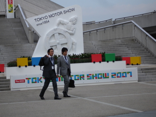 "Japanese ""Salary Men"" Cross in Front of the Motor Show's Statue/Logo"